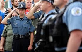 A police explorer salutes as police officials follow Fox Lake Police Lt. Charles Joseph Gliniewicz's family after a vigil at Lakefront Park to honor him.