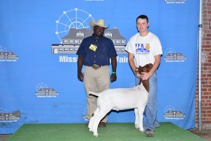 Photo Courtesy of Missouri State Fair:  Spencer Scotten, 21, of Nevada, received Champion Overall and FFA Champion in the FFA Wether Goat Show at the 2014 Missouri State Fair on August 11. Spencer is the son of Shannon and Krista Scotten and is a member of the Nevada FFA Chapter. Pictured with Spencer is Judge Brandon Callis.