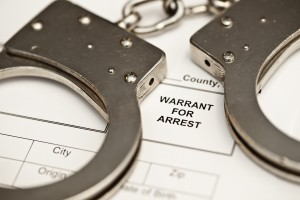 Handcuffs on a warrant for arrest.